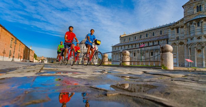 Cyclists on the Piazza dei Miracoli in Pisa
