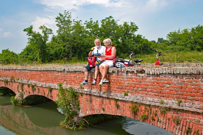 Two cyclists sitting on a small bridge