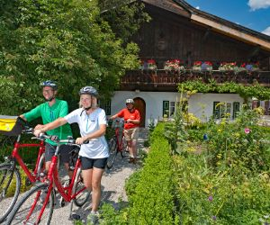 Eurobike-cyclists in front of a beautiful farmhouse in Garmisch Partenkirchen