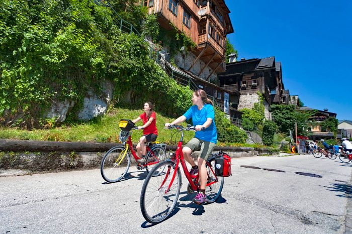 Cyclists in front of antique wooden house in Hallstatt