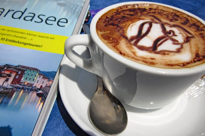Cappuccino next to a travel guide