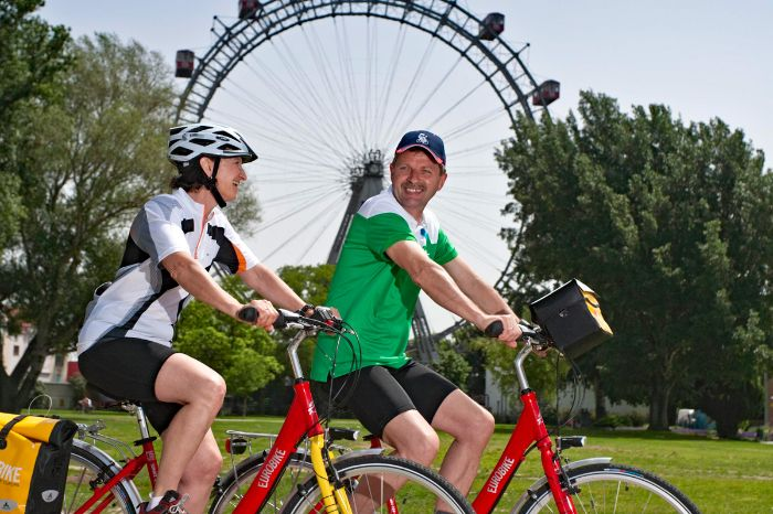 Two cyclists in front of the viennese giant ferris wheel