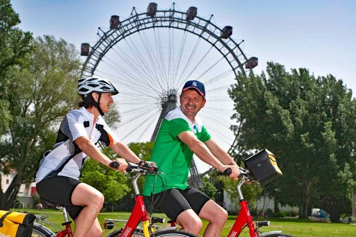 Two cyclists in front of Viennese observation wheel