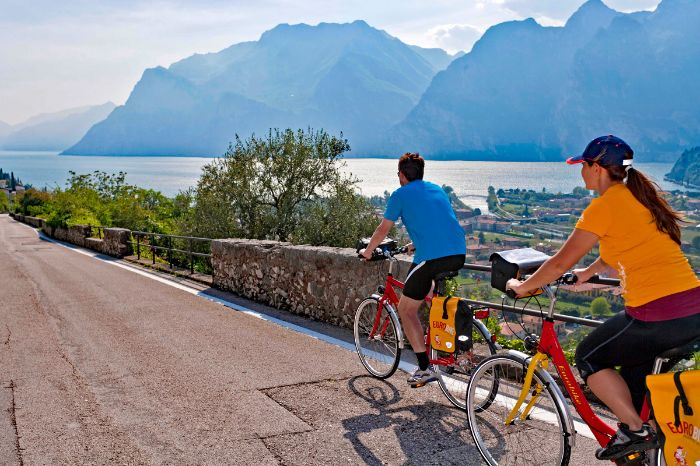 Cyclists on cycle path over Torbole with view over Lake Garda