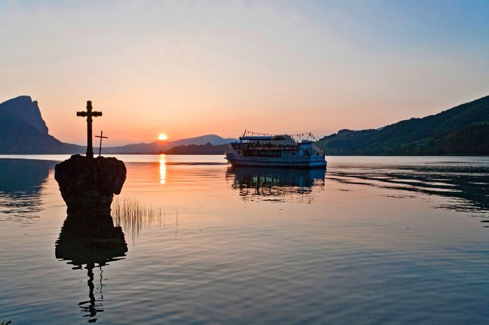 Ship and cross in a rock at sunset at Lake Mondsee