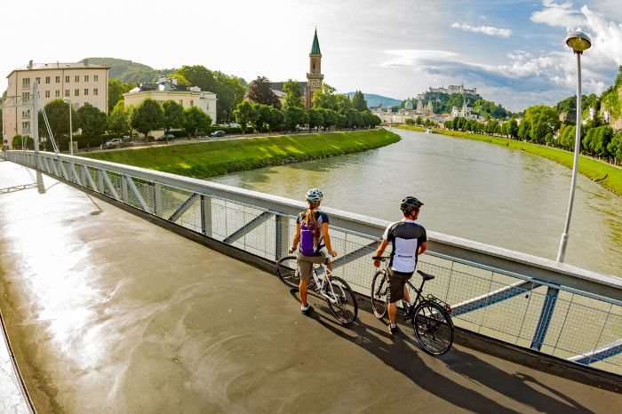 Cyclists looking from bridge over the river Salzach and the historic centre of Salzburg