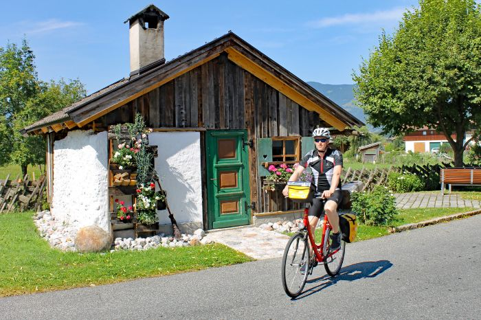Cyclist in front of small wooden cot