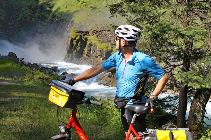 Cyclist in front of waterfalls of Krimml