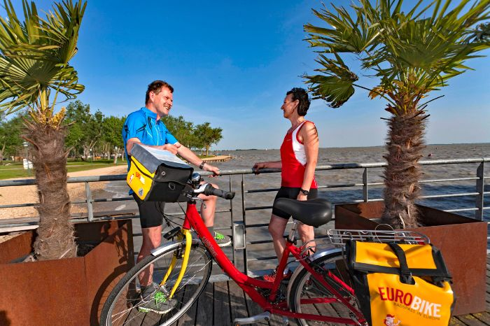 Two cyclists and one Eurobike-bike in front of Lake Neusiedl
