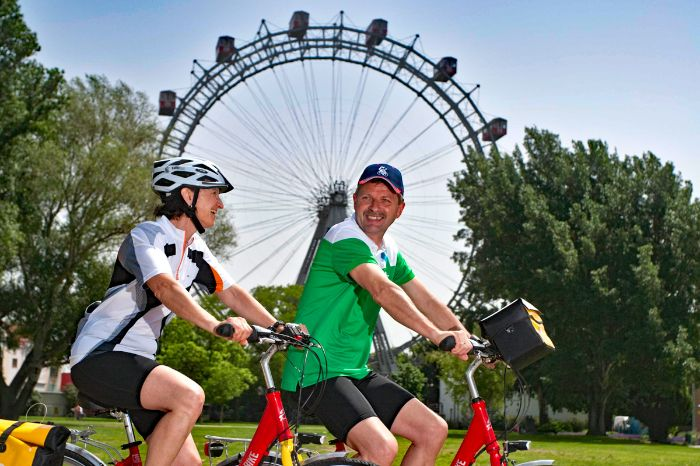 Cyclists in front of Viennese observation wheel