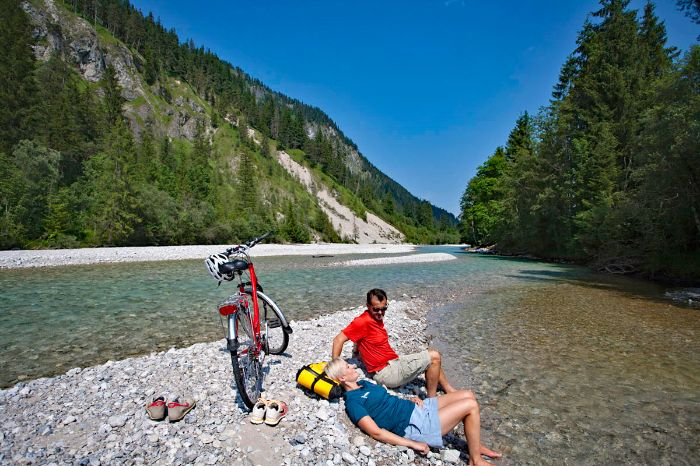 Cyclists having a break on a sandbank in the river Isar
