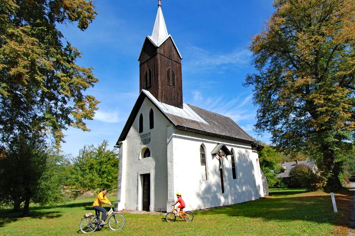 Cyclist in front of small church