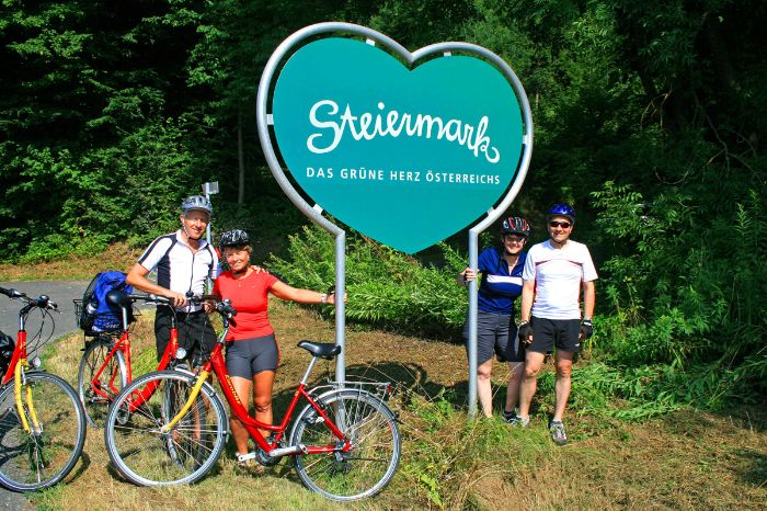 Cyclists in front of the logo of Styria