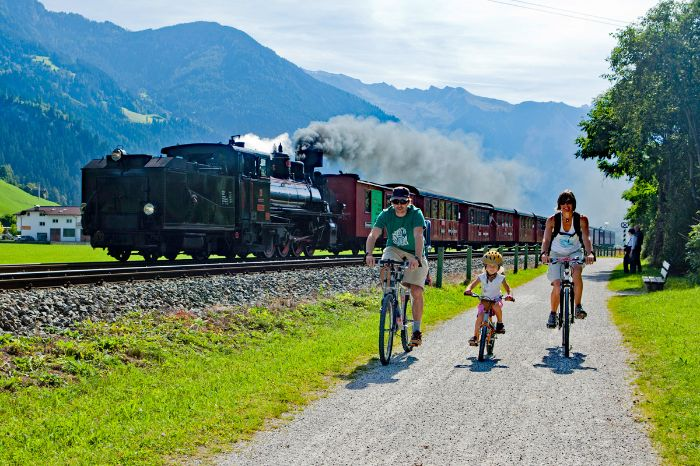 Cyclists next to a steam train