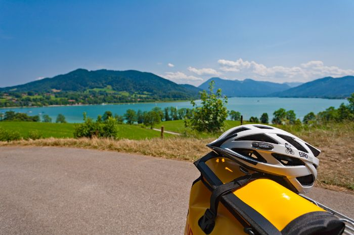 Cycle helmet in front of the scenery of Lake Tegernsee