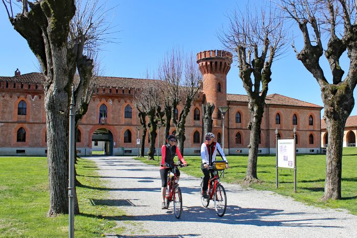 Two cyclists in front of a castle in Pollenzo