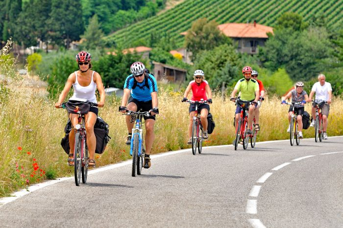 Group of cyclists on a street through tuscany