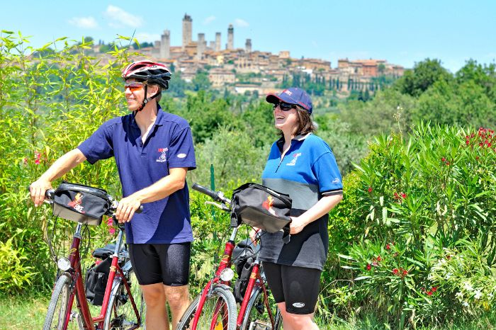 Two cyclists in front of San Gimignano