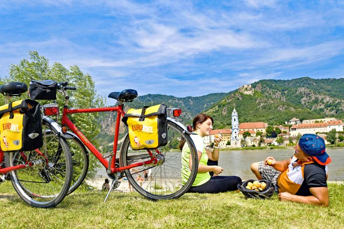 Cyclists having a break at the bank of the river Danube
