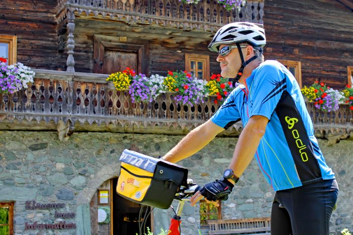 Cyclist in front of wooden house with flowers