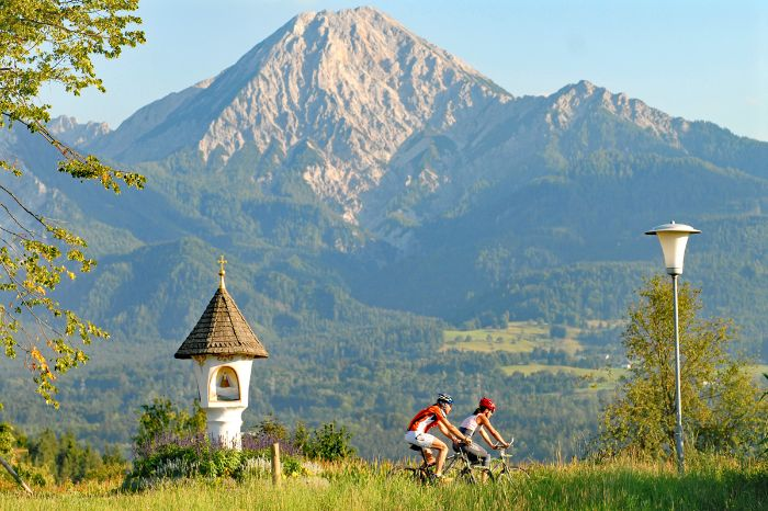 Two cyclists in front of mountain panorama view