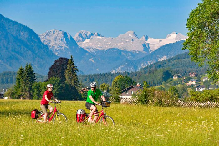 Two cyclists in front of mountain landscape