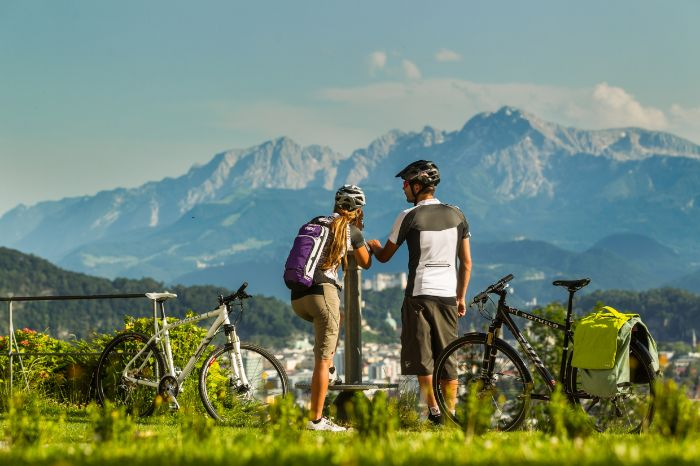 Two cyclists are looking over the mountains