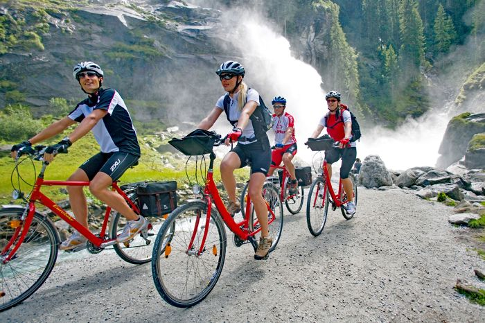 Group of cyclists in front of a waterfall