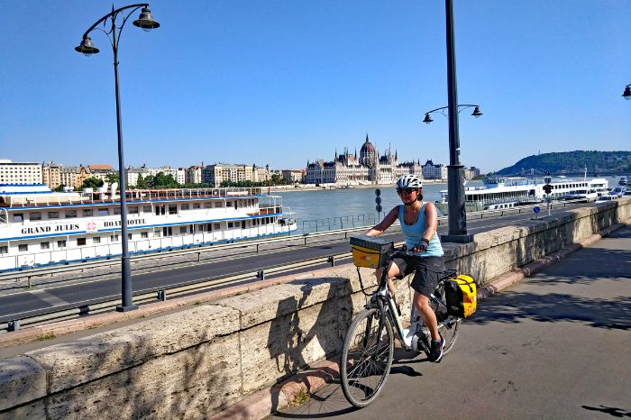 Cyclist in front of the Danube and the Parliament