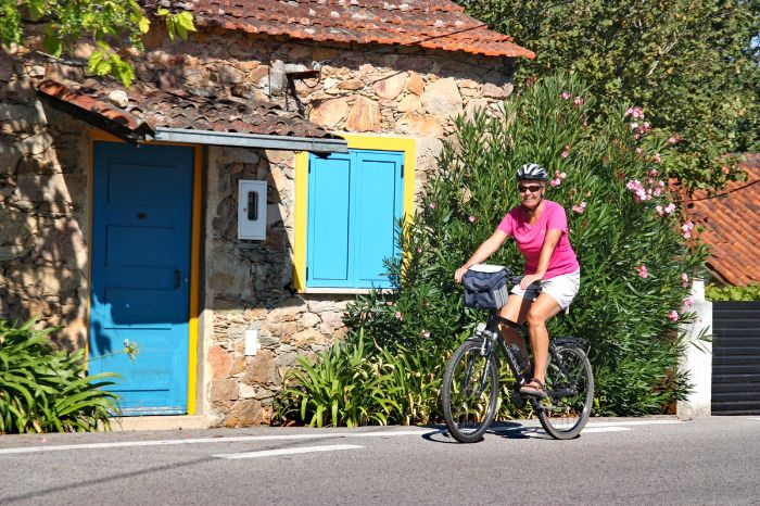 Cyclist in front of house with colorful door and window